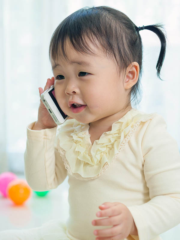 Pretty little Asian girl talking on cell phone.