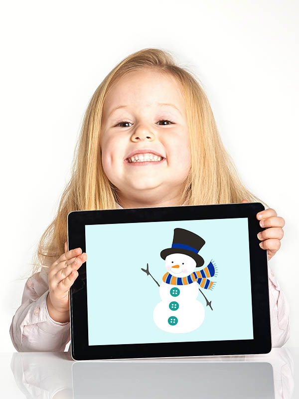 Cute little smiling girl plays with a tablet