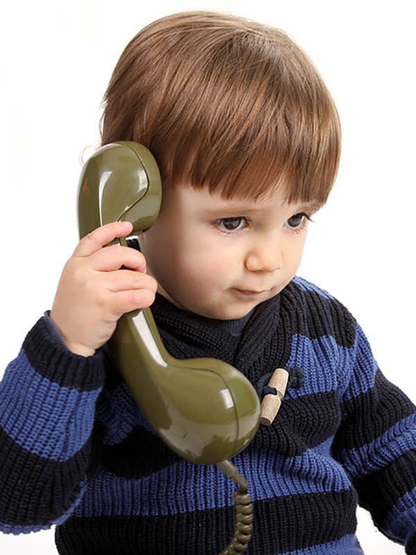 Young boy in a call center with vintage phone.